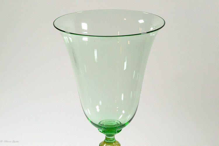 Particolare del bevante di un calice verde in vetro di Murano