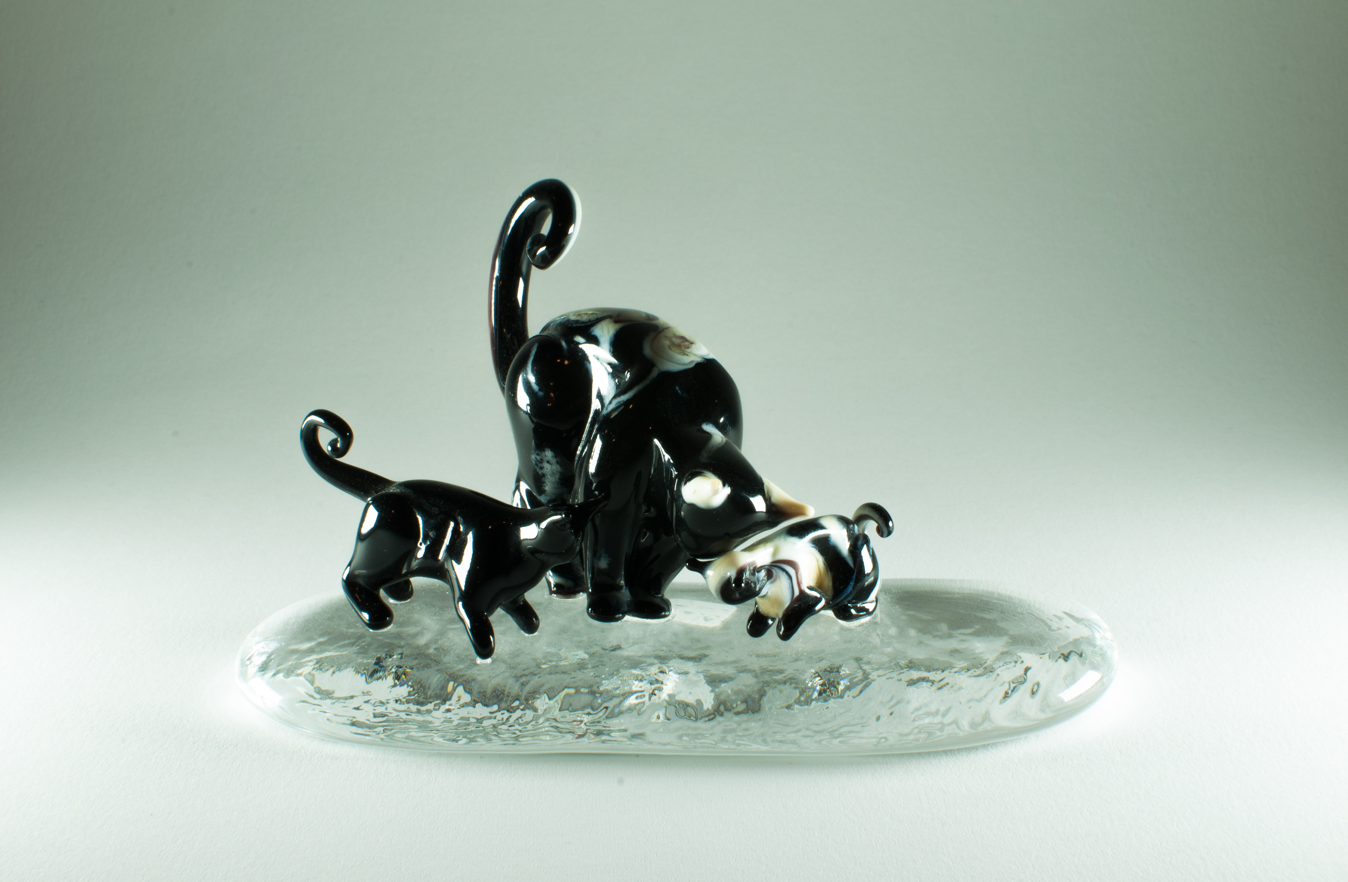 Set of 3 murano glass cats on a glass base