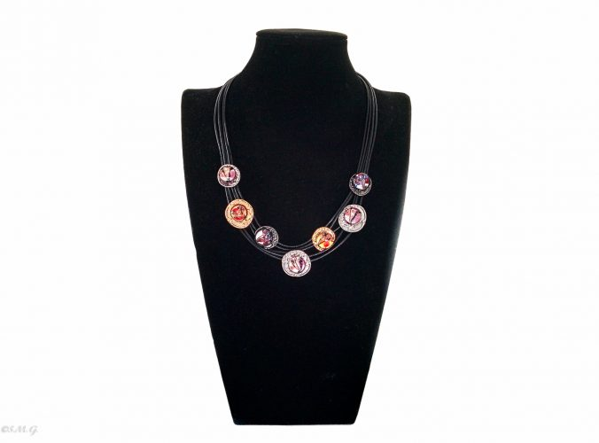 Murano glass necklace with 7 beads on steel discs on a black display